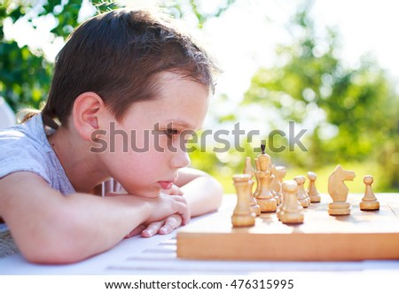 young chess player outdoors. the boy concentrating on the game of chess. view profile