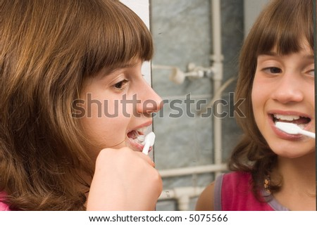 Young child brushing her teeth at mirror - stock photo