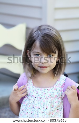 Young child carrying a book bag or back pack leaving home for school. - stock photo