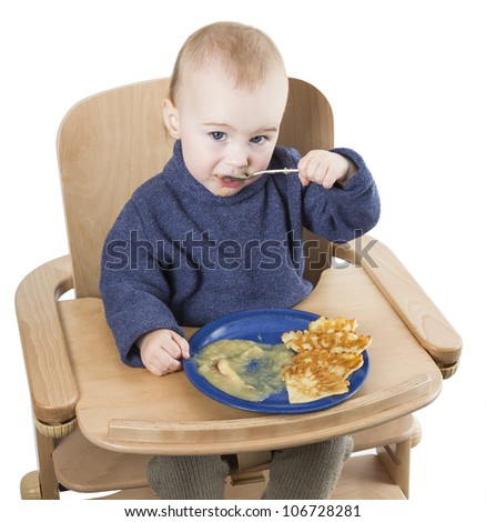 young child eating in high chair isolated in white background