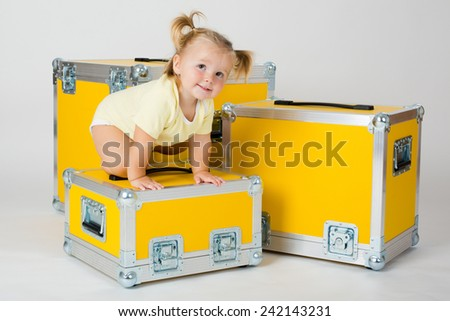Young child girl between yellow road cases (for transporting music and lightning equipment).  - stock photo