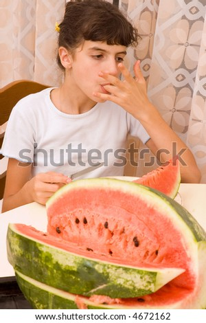 Young child girl eating watermelon in the kitchen - stock photo