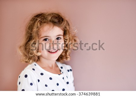 Young child, girl, indoors, against pink background, laughing or smiling. - stock photo