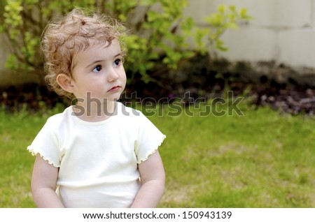 Young child, girl toddler, outdoors. She has blonde curly hair and wearing a plain light colour top. She looks deep in thought, day dreaming or pensive. Could also be sad and alone.  - stock photo