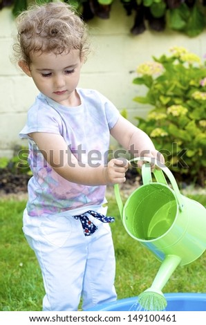 Young child, girl toddler, playing in a garden with a green watering can. She is wearing white trousers and a coloured top and has blonde curly hair. Backdrop of green grass and plants. - stock photo