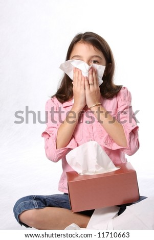 young child / girl with cold - sneezing and blowing nose with tissues