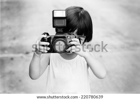 young child holding a old camera