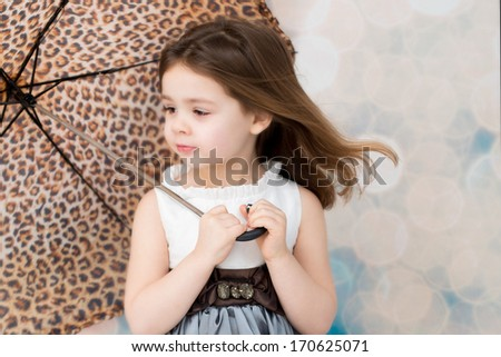 Young child holding an umbrella. - stock photo