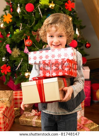 Young child holding gifts in front of Christmas tree - stock photo