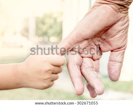 Young child holding her grandparent for the hand,selective focus  - stock photo