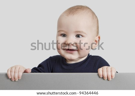 young child holding sign. isolate on grey background