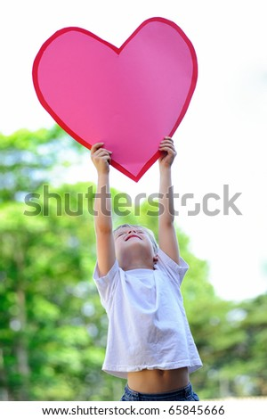 Young child holds a big pink paper heart - stock photo