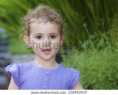 Young child in garden. A pretty girl, toddler, wearing a lilac purple top. Head and shoulders shot, with green backdrop of garden. She has blonde curly hair and a good expression.  - stock photo