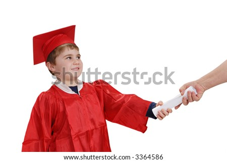Young child, in red graduation robe and cap, smiling while receiving his diploma - stock photo