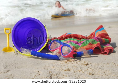 young child in water having fun at beach with toys in sand - stock photo