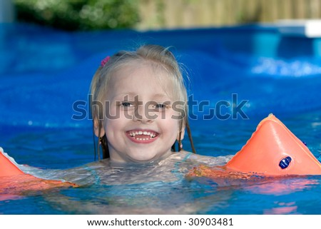 Young child is swimming in the pool - stock photo