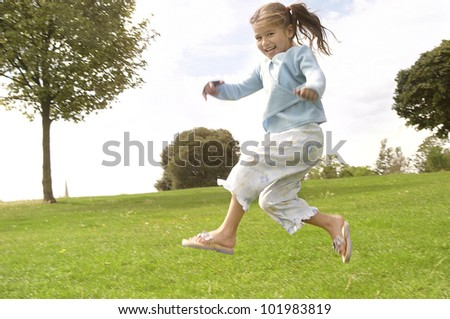 Young child jumping in the park. - stock photo