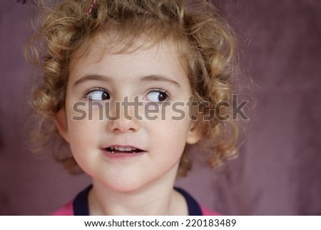 Young child looking cheeky, with a fun expression. - stock photo