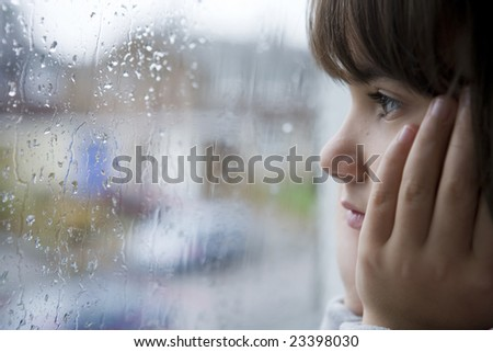 young child looking out of window on rainy day - stock photo