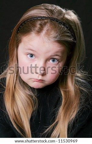 young child looking upset over a black background