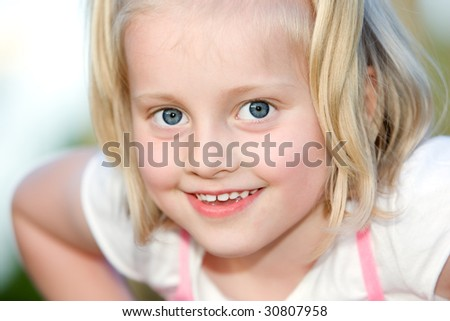 Young child looks happy into the camera - stock photo