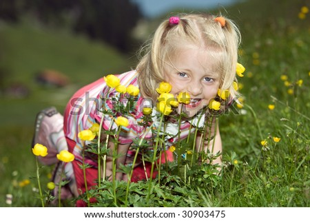 Young child on a meadow with flowers smiles into camera - stock photo