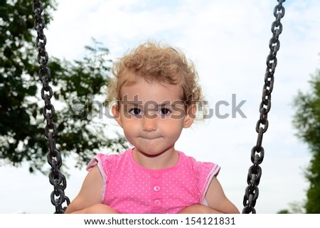 Young child on a swing at the park. Toddler girl smiling on a swing at the playground. She is wearing pink top and has blonde curly hair. Low viewpoint with white cloudy sky and trees background. - stock photo
