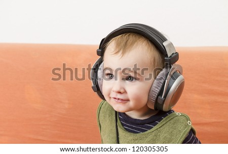 young child on couch with big earphone - stock photo