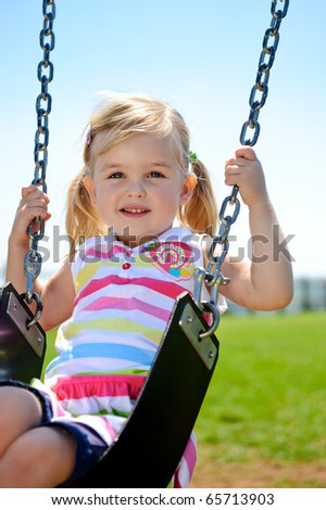 Young child on swing in playground outdoors - stock photo