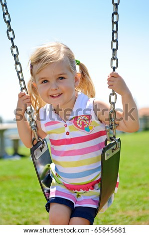Young child on swing in playground outdoors