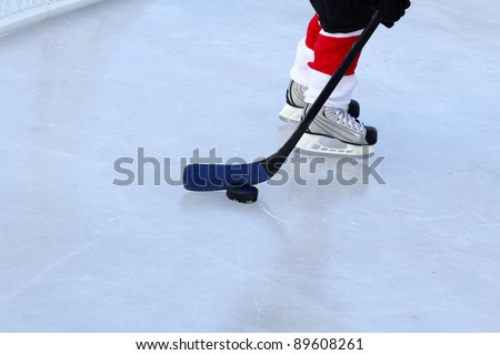 Young child playing ice hockey on a pond - stock photo
