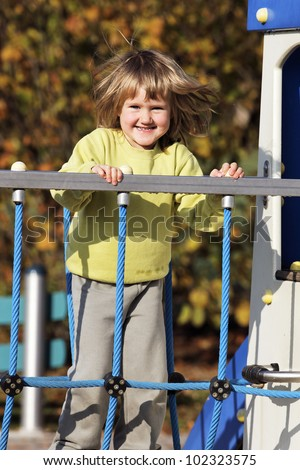 young child playing on colorful playground in autumn - stock photo