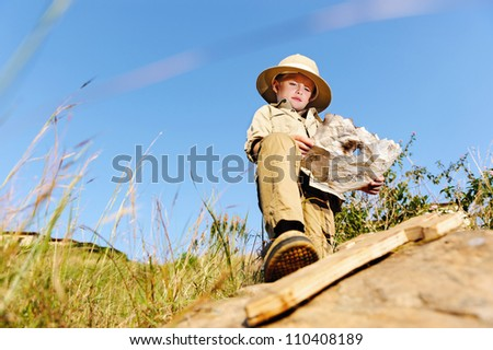 young child playing pretend adventure explorer with wooden sword and treasure map. - stock photo