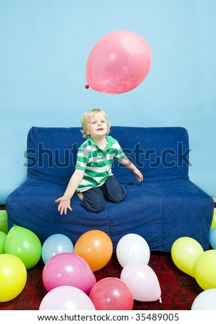Young child playing with balloons on a couch - stock photo