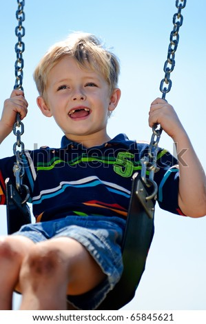 Young child plays on swing in the outdoor playground - stock photo