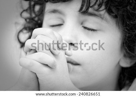 Young child praying  intensely and with reverence to God during his daily devotional, Christian boy relationship with Jesus. Black and white image - stock photo