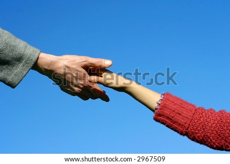 Young child's hand reaching out towards an adult, shot against beautiful blue sky. - stock photo