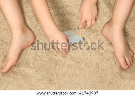Young child's hands and feet in sand playing with credit card.