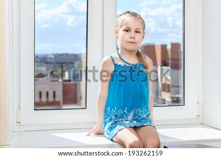 Young child sitting in middle of window sill - stock photo