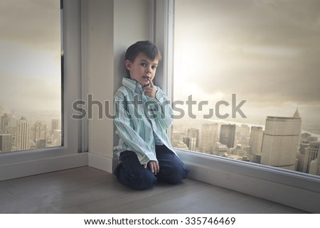 Young child sitting in the corner of a room - stock photo