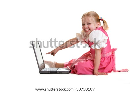 Young child sitting on computer and smiles - stock photo
