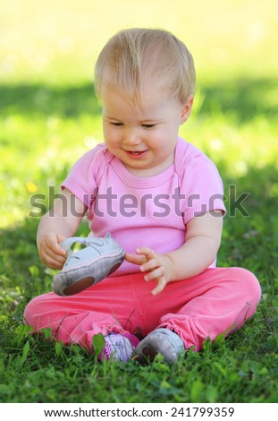 Young child sitting on grass - stock photo