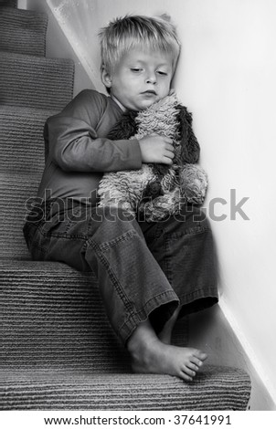 Young Child sitting on the stairs looking troubled. - stock photo
