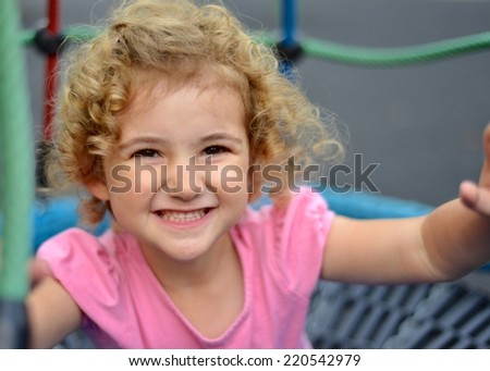 Young child smiling whilst playing outdoors. - stock photo