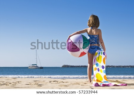 Young child standing with beachball and towel ready to play. - stock photo