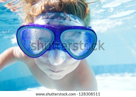 young child swimming underwater in pool - stock photo