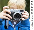 Young child, taking a picture using a retro rangefinder camera - stock photo