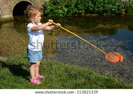 Young child, toddler girl fishing in a stream with a fishing net and rod. She is wearing blue shorts and a white t-shirt. - stock photo
