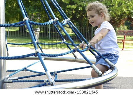 Young child, toddler, girl, playing at the park. She is on a rope swing roundabout at the playground. She is blonde and wearing blue shorts and white t-shirt. - stock photo