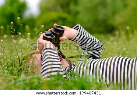 Young child using a pair of binoculars to look up into the sky as he lies on back in a grassy rural meadow enjoying a day in nature - stock photo